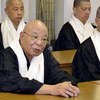 Hosed: Kosho Shono (left), leader of Koyasan Shingon Buddhism, speaks at a press conference Wednesday at the temple's headquarters in Koya, Wakayama Prefecture. Shono announced his resignation to take responsibility for financial losses at the temple, which saw about a quarter of its assets vanish as bets on the Australian dollar and structured bonds soured. | KYODO