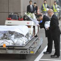 The war goes on: Koichi Kawana (right), president of engineering firm JGC Corp., and another JGC official place flowers on the coffins of fellow employees killed by terrorists in Algeria in January. A government panel is to submit proposals Friday to increase compensation for those caught up in terrorist attacks abroad. | KYODO