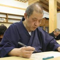Heart set: Takashi Nagahama, a trainee priest, copies the Heart Sutra at Shogen Junior College in Minokamo, Gifu Prefecture, earlier this month. | CHUNICHI SHIMBUN
