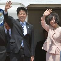 All business: Prime Minister Shinzo Abe and his wife, Akie, wave to well-wishers upon his departure from Haneda airport on Sunday. Abe will visit Russia, the Middle East and Turkey. | AFP-JIJI