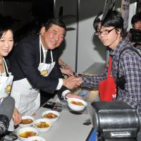 Serving the people: Liberal Democratic Party lawmaker Yuriko Koike (left) and LDP Secretary General Shigeru Ishiba (center) smile as they serve curry and greet a young visitor to their booth at the Nico Nico Douga event at Makuhari Messe in Chiba on Sunday. | YOSHIAKI MIURA