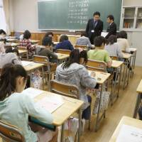 Skills check: Students take the national achievement examination at an elementary school in Tokyo on Wednesday. 