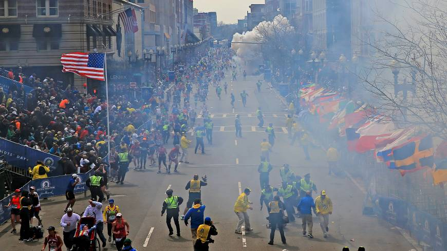 Sudden impact: People react as a bomb explodes Monday near the finish line of the 2013 Boston Marathon.  Two explosions went off near the finish line, sending authorities out onto the course to carry off the wounded while the stragglers were rerouted away from the smoking site of the blasts.