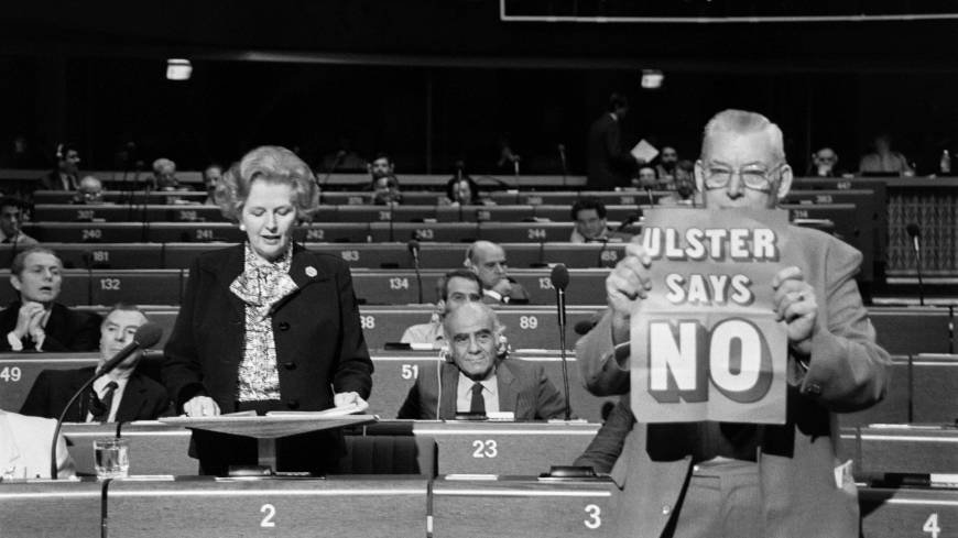 Margaret Thatcher addresses the European Parliament in Strasbourg in December 1986 as Democratic Unionist Party leader Ian Paisley brandishes a placard reading: 'Ulster says no.'