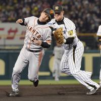 Got you: Hanshin third baseman tags out the Giants' Kazunari Sanematsu on Thursday at Koshien Stadium. The Tigers won 3-0. | AP
