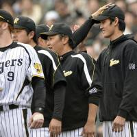 Rookie Shintaro Fujinami gets a pat on the head from a fellow Hanshin Tiger player Sunday after six shutout innings in his home debut. | KYODO