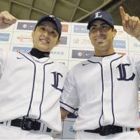 Twin towers: Seibu's Ryoma Nogami (left) and Ryan Spilborghs celebrate after the Lions' 7-2 win over the Marines on Wednesday. | KYODO