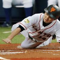 It's a dirty job: Giants pitcher Toshiya Sugiuchi slides safely into home during the Kyojin's 17-1 win over the BayStars. | KYODO