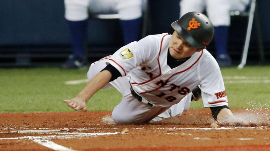 It's a dirty job: Giants pitcher Toshiya Sugiuchi slides safely into home during the Kyojin's 17-1 win over the BayStars.