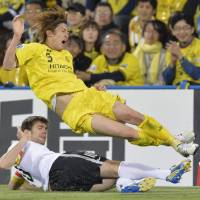 Collision course: Tatsuya Masushima of Kashiwa Reysol and a Guizhou Renhe player vie for the ball during Tuesday's Asian Champions League match in Kashiwa, Chiba Prefecture. The match ended in a 1-1 draw. | KYODO