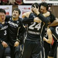In it together: Aisin players celebrate after beating Toshiba 58-54 in Game 5 of the JBL Finals on Monday to clinch the championship. | KYODO