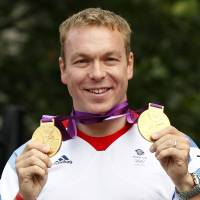 National icon: Cyclist Chris Hoy holds up his two of his British record six Olympic gold medals during a September parade celebrating Britain's athletes who competed in the 2012 Olympic and Paralympic Games in central London. | AFP-JIJI