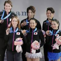 Team effort: Japanese figure skaters stand together during the awards ceremony after receiving their third-place medals at the World Team Trophy on Saturday. | KYODO