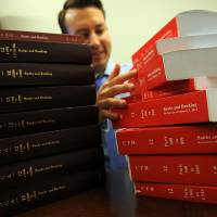 Bedtime reading: Federal lawyer Kevin Korzeniewski stands behind stacks of copies of the U.S. legal code, which he thinks the government can live without, in his office in  Washington. His suggestion that federal agencies access the information online was one of 86,000 budget-cutting ideas suggested in response to a White House request. | THE WASHINGTON POST