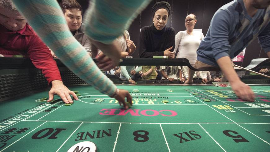 Maintaining focus: From left, students Carl Smith, Karl Kim and Dana Trantham work the craps table while student Ashley Fletcher observes during class at the Casino Dealer School in Glen Burnie, Maryland, on Feb. 28. Dealers are needed as new live-action table games launch in Maryland on Thursday.