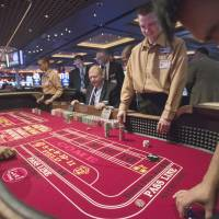 Action: Casino school student Tommie Alexander (left) runs a craps table for the first time at Maryland Live Casino in Hanover, Maryland, on April 5, joined by classmates in the same uniform, Dana Trantham (center) and Darren Rice. | THE WASHINGTON POST