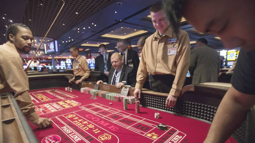 Action: Casino school student Tommie Alexander (left) runs a craps table for the first time at Maryland Live Casino in Hanover, Maryland, on April 5, joined by classmates in the same uniform, Dana Trantham (center) and Darren Rice.