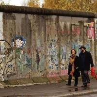 Off the wall: Pedestrians pass in front of a remaining section of the Berlin Wall in November 2005. Chunks of the Iron Curtain icon are now displayed at the headquarters of the U.N. in New York, at a casino in Las Vegas and at Microsoft's headquarters in Washington state. | THE WASHINGTON POST
