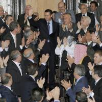 Still standing: Syrian President Bashar Assad waves as he greets lawmakers before a March 2011 speech to Parliament. | AP