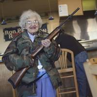 A gun for everyone: An elderly woman holds a semi-automatic rifle at a pizza outlet in Virginia Beach, Virginia, in February. | AP