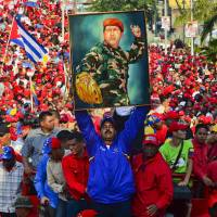 Trump card: Nicolas Maduro, Venezuela's interim president, holds a picture of the late Hugo Chavez during a campaign rally in the port city of Catia La Mar, in northern Vargas state, on Tuesday. | AFP-JIJI