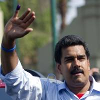 Like 'father': Newly elected Venezuelan President Nicolas Maduro waves to supporters after casting his vote in Caracas on Sunday. | AFP-JIJI
