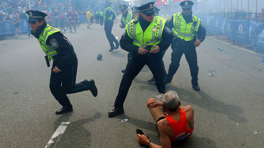 City under attack: A man lies on the ground as police officers react to a second explosion at the finish line of the Boston Marathon in the city Monday.