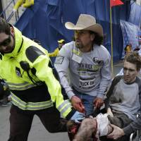 The cowboy way: An emergency responder and volunteers, including Carlos Arredondo in the cowboy hat, push Jeff Bauman in a wheelchair after he was badly injured in an explosion near the finish line of the Boston Marathon on Monday. | AP