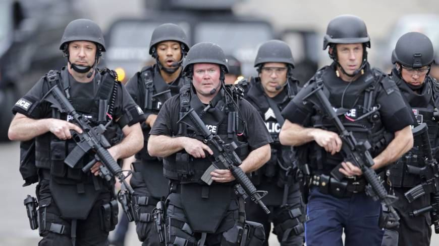Defend the homeland: A SWAT team marches through a neighborhood while searching for a suspect in the Boston Marathon bombing in Watertown, Massachusetts, on Friday.