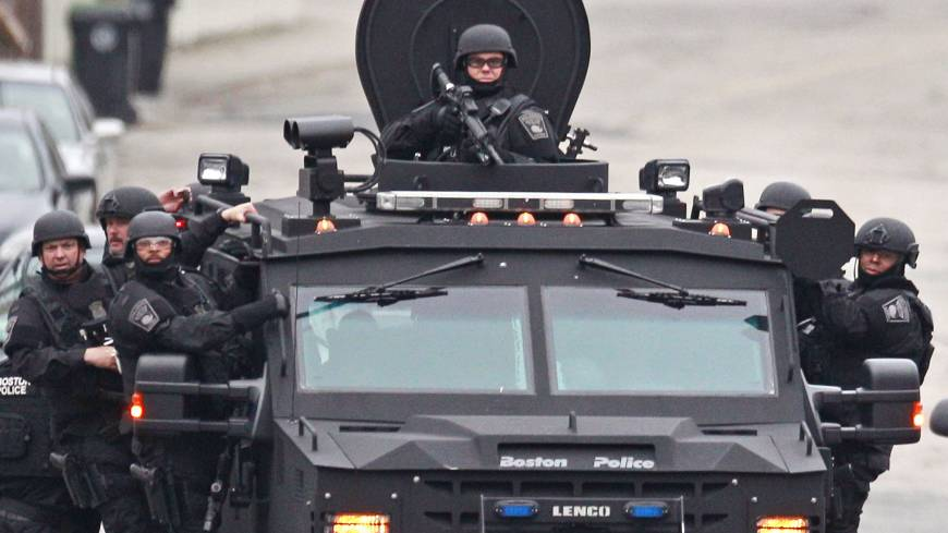 Heavily armed police patrol a neighborhood in the suburb while riding on an armored Humvee the same day.
