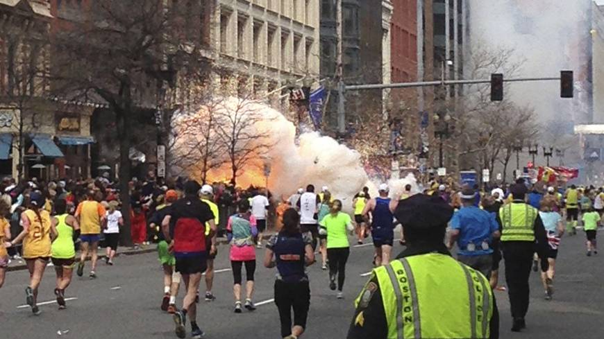 Crossing the line: Runners make their way to the finish line of the Boston Marathon as a bomb explodes on April 15. Two explosions, about 10 seconds apart, ripped through the crowd, killing three and seriously wounding scores.