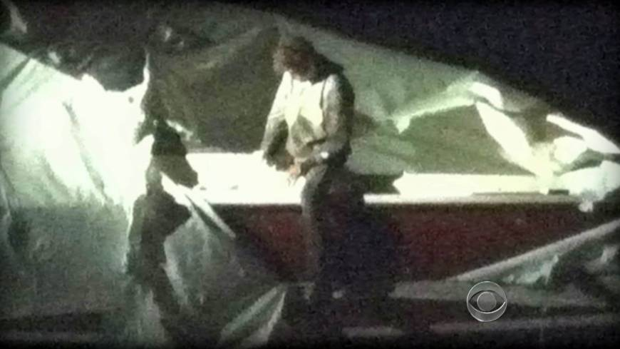 High and dry: Dzhokhar Tsarnaev, a suspect in the Boston Marathon bombing, leaves the boat he was hiding in after being confronted by police in the suburb of Watertown, Massachusetts, on Friday.