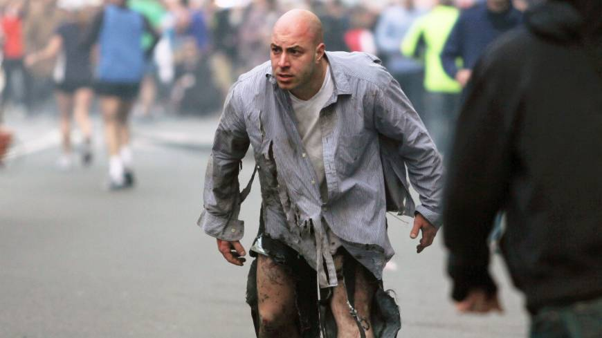A man, whose clothes were shredded in the bombing, stumbles away from the scene of the two explosions on April 15.