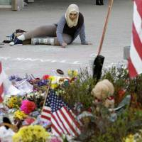 Comforting words: Massachusetts Institute of Technology student Hajar Boughoula, from Bizerte, Tunisia, writes a message on the ground with chalk near a makeshift memorial for fallen MIT police officer Sean Collier on the school's campus in Cambridge, Massachusetts, on Monday. | AP