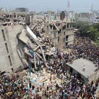 Looking to help: People gather after an eight-story building collapsed in Savar, near Dhaka, on Wednesday. | AP