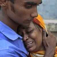 Weight of the world: Relatives mourn a victim at the site of a building collapse Wednesday in Savar, near Dhaka. | AP