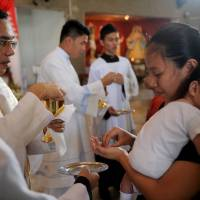 Communion and community: A Catholic receives sacred bread during a Mass held at a small church in Manila on April 21. | AFP-JIJI