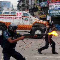 Disperse: Police fire rubber bullets toward protesters during clashes with Islamists in Dhaka on Sunday. | AFP-JIJI