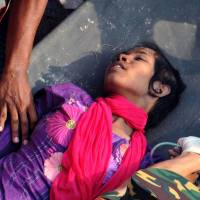 Fighter: Reshma Begum, 18, is carried on a stretcher out of a collapsed building in Savar, on the outskirts of Dhaka, on Friday. Rescuers had located her buried in the rubble of the garment factory complex, where the seamstress had been trapped for 17 days. | AFP-JIJI