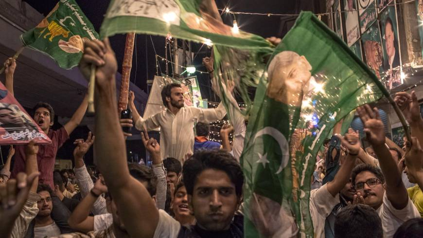 Green grins: Supporters of the Pakistan Muslim League-N party celebrate election results in Lahore on Saturday.