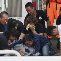 Last port of call: Family members cry around the body of Hung Shih-cheng after his boat arrived back at Liuqiu port in southern Taiwan on Saturday. | AP
