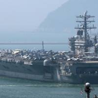 Just training: The aircraft carrier USS Nimitz leaves the southern port city of Busan, South Korea, on Monday. North Korea slammed joint naval drills by the United States and South Korea involving the carrier last week. | AFP-JIJI