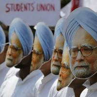 In your face: Student activists wear masks of Indian Prime Minister Manmohan Singh during a protest against the leader in the city of Gauhati on Wednesday. | AP