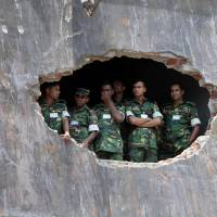 In memory: Bangladeshi soldiers observe an Islamic prayer ceremony May 14 for the souls of the 1,127 people who died when a building housing garment factories collapsed last month in Savar, near Dhaka. | AP