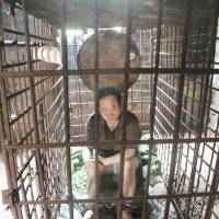 Shackled:  Wu  Yuanhong on Friday sits in the cage his family has kept him in for over a decade in Jiangxi province, China. | AFP-JIJI