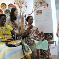 Rwandan women demonstrate how to weave traditional baskets, which are exported to Japan, at African Fair 2013 in Yokohama on Thursday. The fair will run through Sunday. | SATOKO KAWASAKI