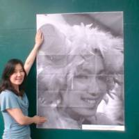 Poster women: Aya Suzuki puts up a poster of Naho Iguchi on a wall in a Meguro-ku children's playground. Both women are volunteers, organizing free public lecture events through TEDxTokyo. | COURTESY OF