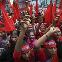Fashion victims: Women protesters shout slogans calling for better working conditions for garment workers during a May Day rally on May 1 in Dhaka, Bangladesh. Thousands of garment factory workers paraded through the streets of the city calling for safeguards to be put in place after a factory building collapsed last month, killing more than 1,100 people. | AP
