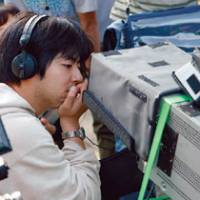 Quiet on the set: Director Yuya Ishii examines a shot through a monitor on the set of his latest film, 'Azemichi no Dandy.' | (C) 2011