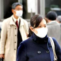 Air conditioning: Two of Tokyo's millions of pollen-allergy sufferers use masks to aid their plight. | SATOKO KAWSAKI PHOTO